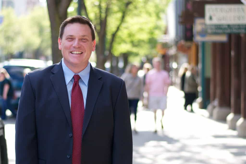 Attorney Matthew Benedict wearing suit walking in downtown Traverse City.